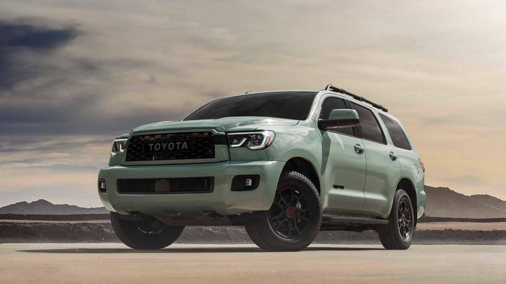 a 2021 toyota sequoia trd pro in Lunar rock in a pale desert showing off its wide, rugged stance.