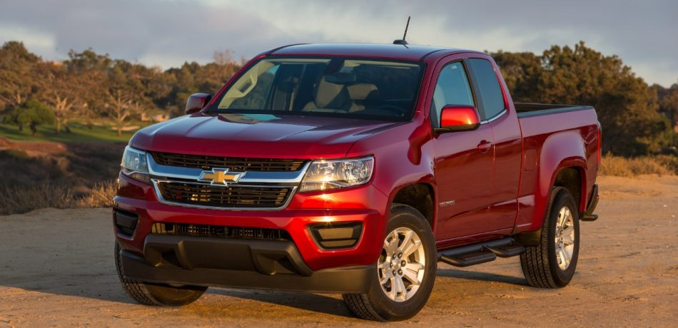 a red 2018 Chevrolet Colorado parked on the sand with a mountainous backdrop