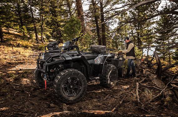 a 2021 Polaris Sportsman XP 1000 ATV towing and hauling in a wooded area