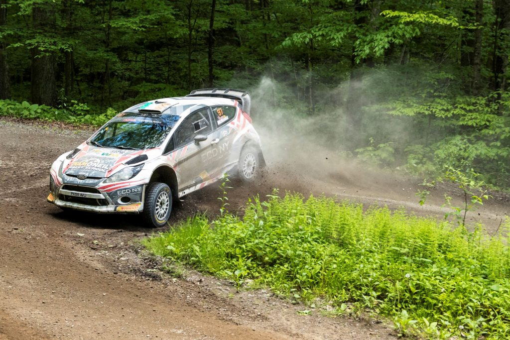 The white #97 Ford Fiesta slides on a dirt forest trail at the 2017 Susquehannock Trail Performance Rally in Pennsylvania