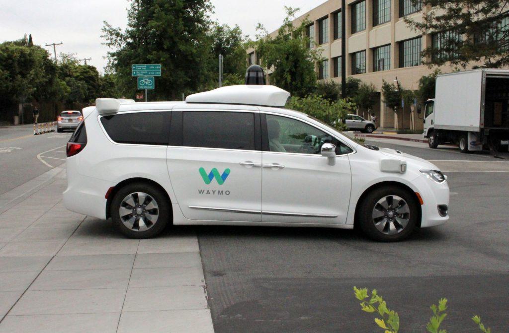 A white Waymo autonomous test car pulls into the company's California headquarters