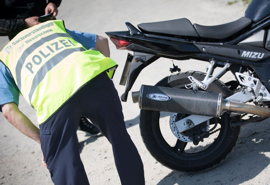 A German police officer in a high-vis jacket checks how loud a black motorcycle's exhaust pipe is