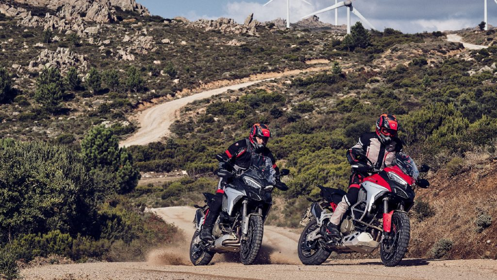 Two riders on a red-and-silver and a black-and-silver A red and a black 2021 Ducati Multistrada V4 S in the desert hills
