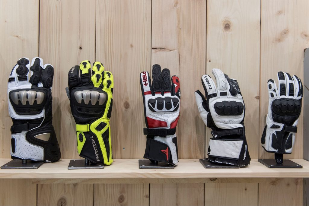 A selection of gauntlet-style motorcycle gloves on display on a wooden stand
