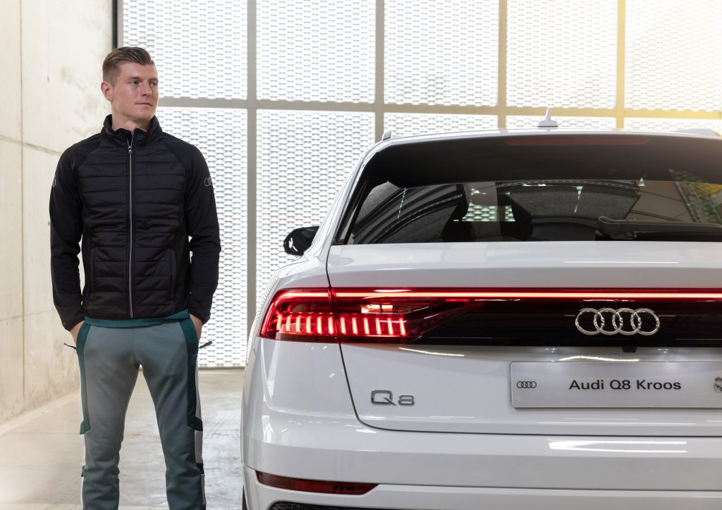 Toni Kroos stands next to a new white Audi Q8