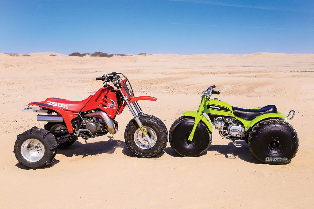 one red and one green three-wheeler ATV on display in the desert
