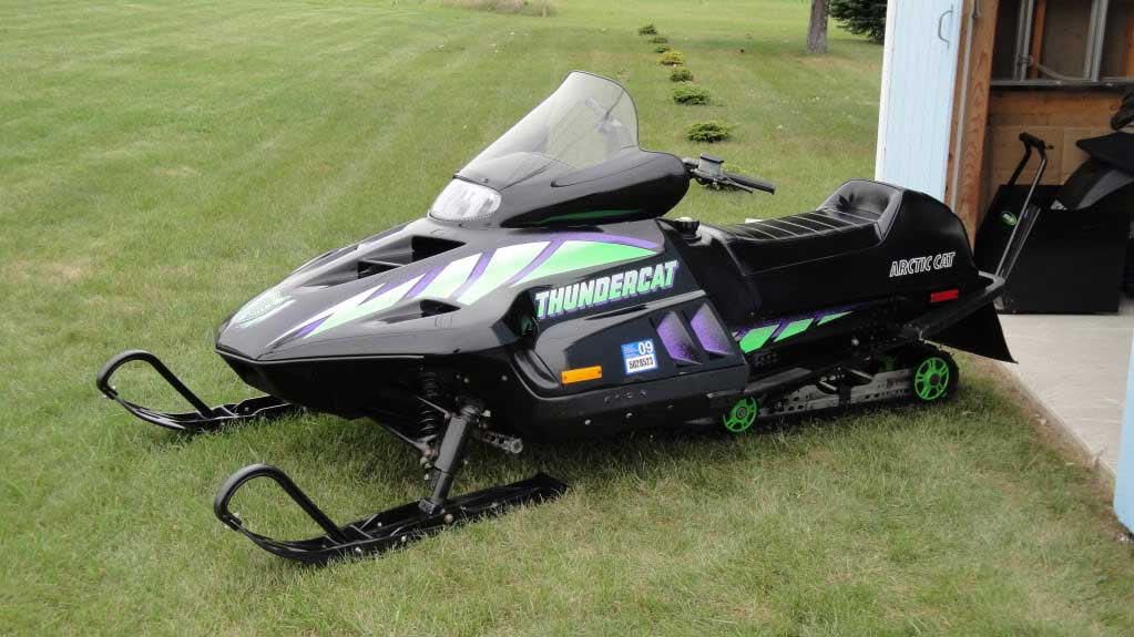 a throwback 1990s Arctic Cat Thundercat in the grass on display in the off-season