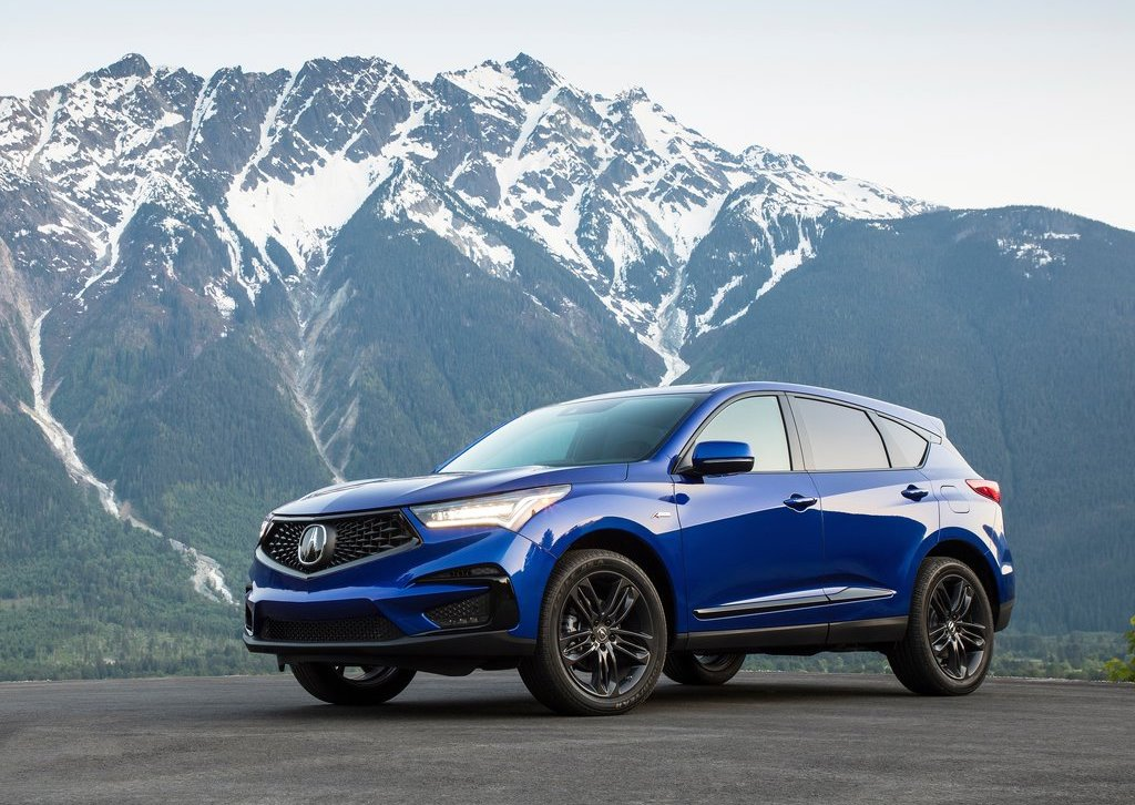 a front shot of a blue 2019 Acura RDX in front of a mountain range