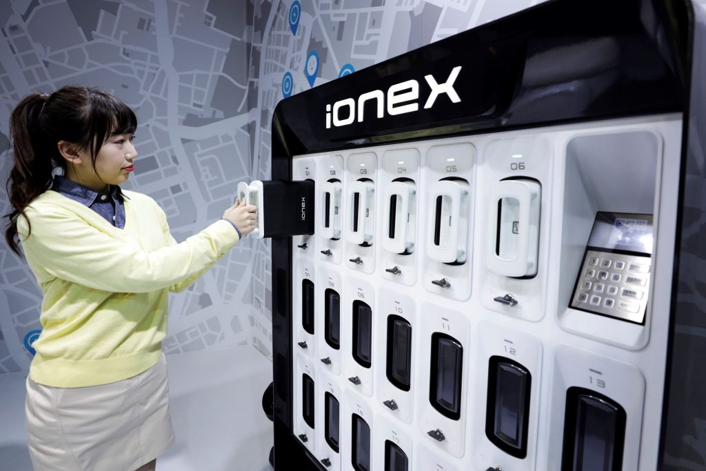 An attendant demonstrates the Kymco Ionex battery swap station