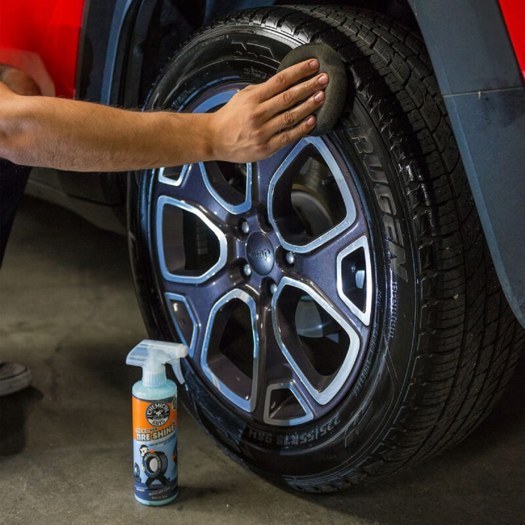 A worker applies Chemical Guys Tire Kicker tire shine