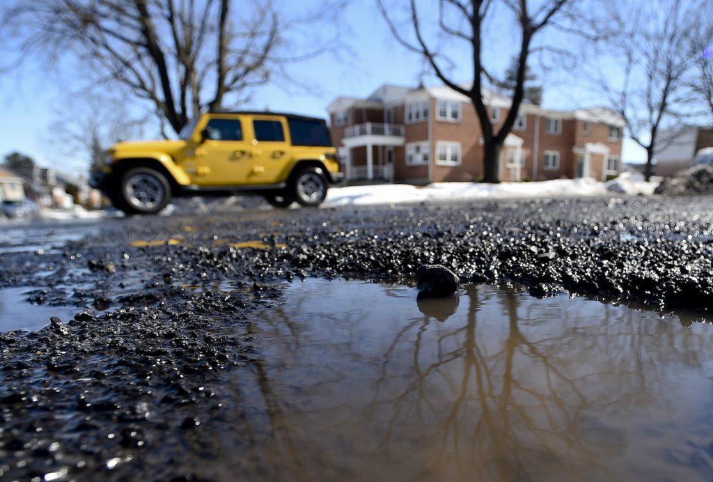 A Jeep Wrangler avoids hitting a pothole on a street.
