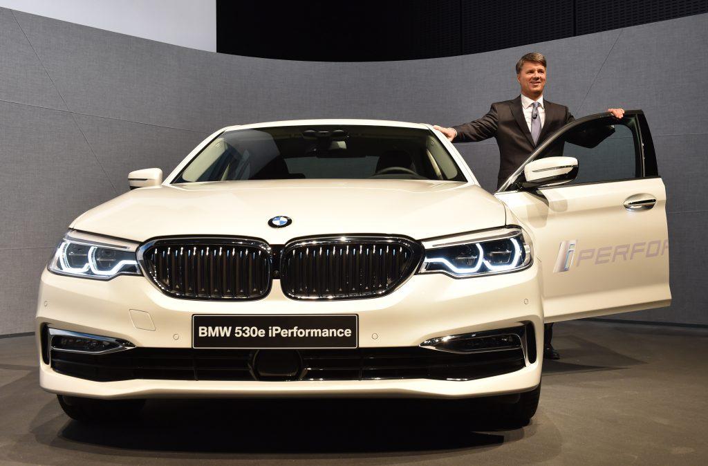 A BMW employee poses next to a 530e