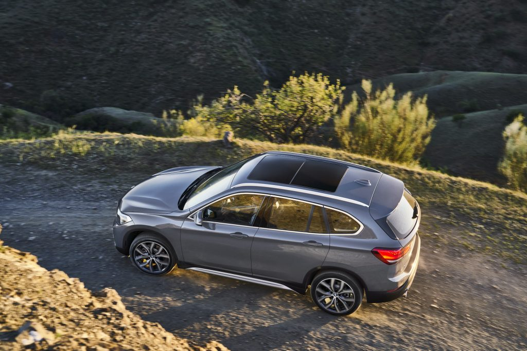 A gray BMW X1 luxury SUV travels on a dirt road on a mountain