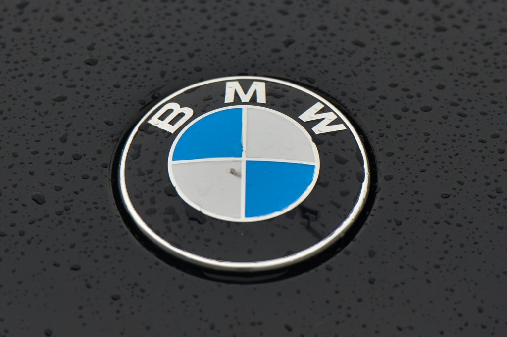 A raindrop-dotted BMW logo on a parked black car
