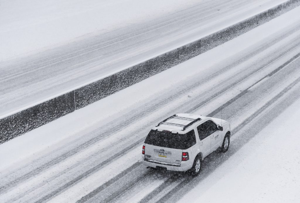 A white Ford Expedition SUV travels on a snowy highway.