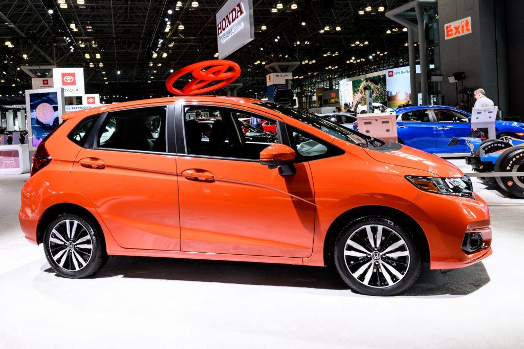 An orange 2016 Honda Fit sits on display