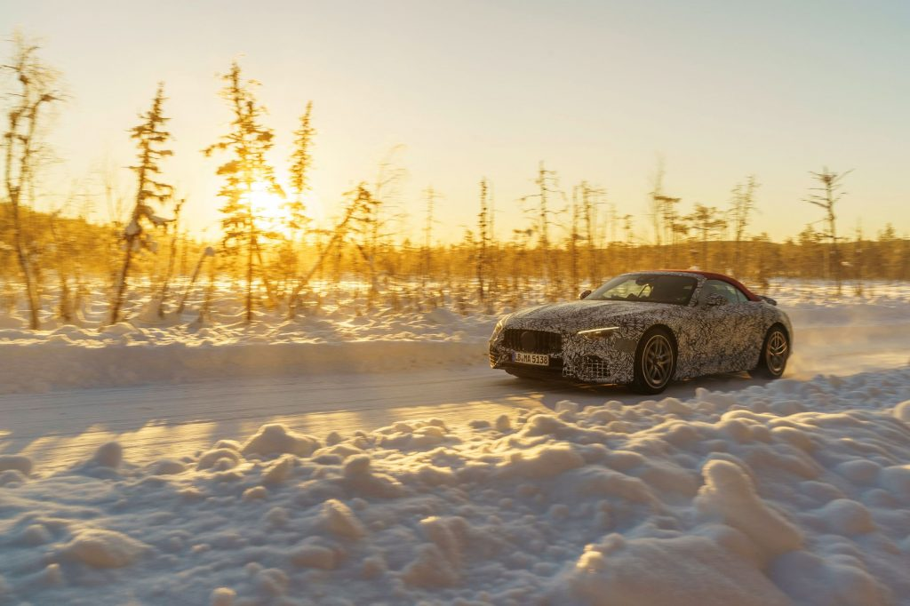 A camouflaged 2022 Mercedes-AMG SL with a red roof undergoing winter testing