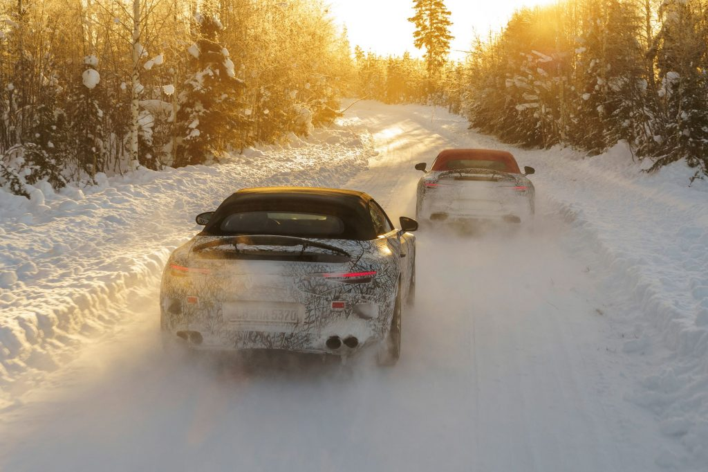 The rear view of a black-roofed and a red-roofed camouflaged 2022 Mercedes-AMG SL driving through a snow-covered forest