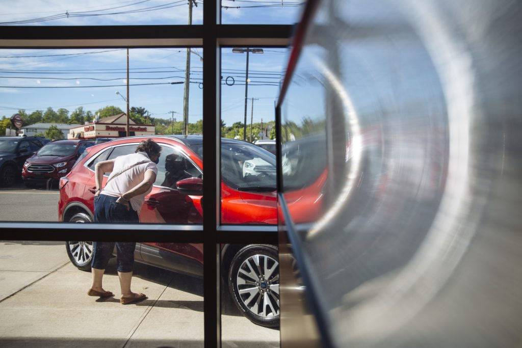 A potential customer looks in the window a new red car at a dealership.
