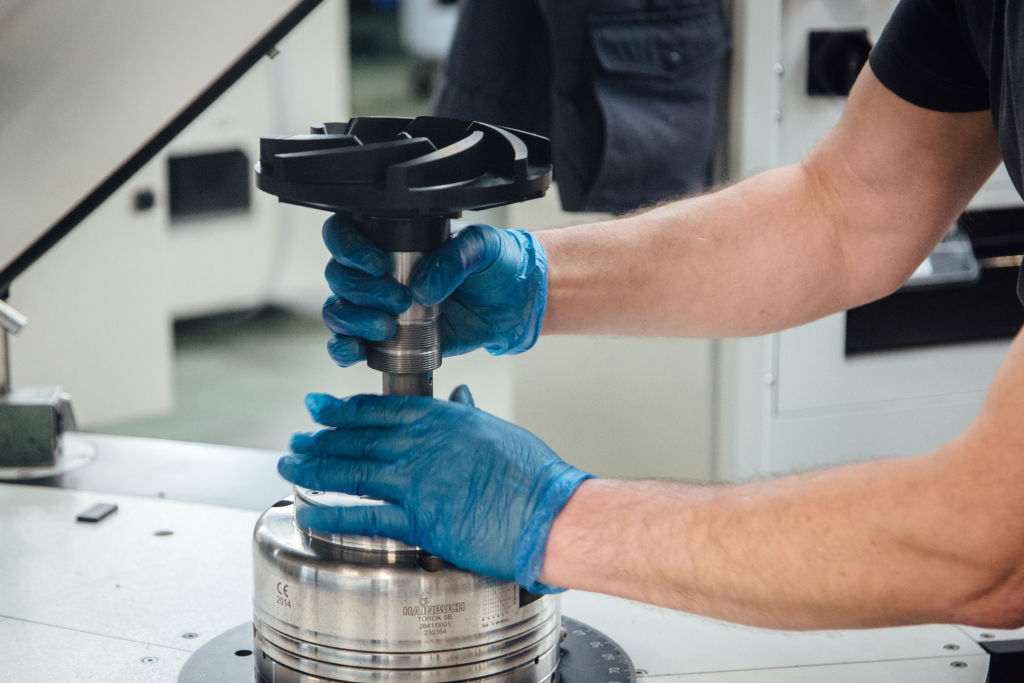 A technician assembles a centrifugal pump impeller on a work bench