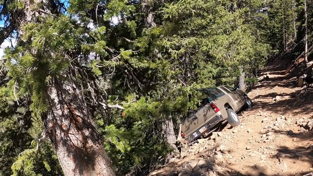 A very stuck Chevy Silverado stuck on the side of a cliff