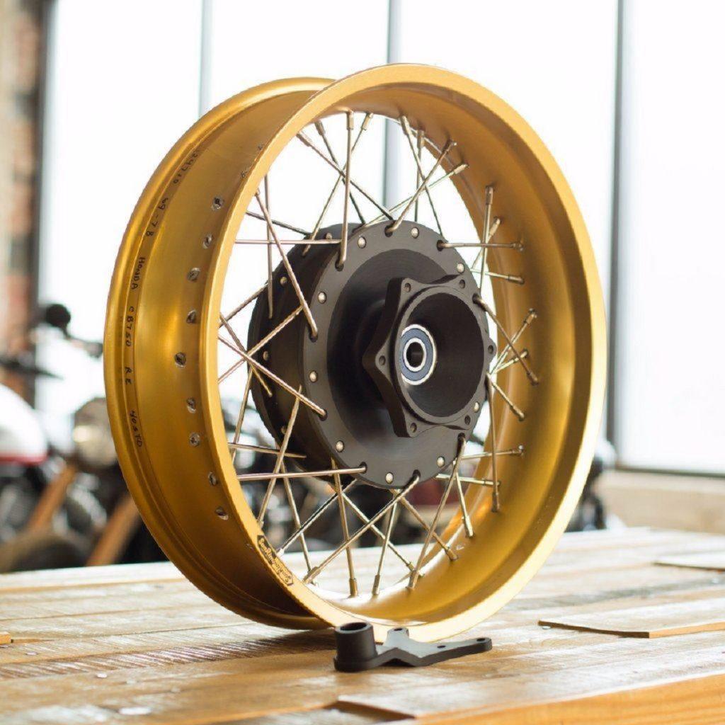 A gold Sun wheel for a 1969-1982 Honda CB750 with a black Cognito Moto disc brake conversion hub