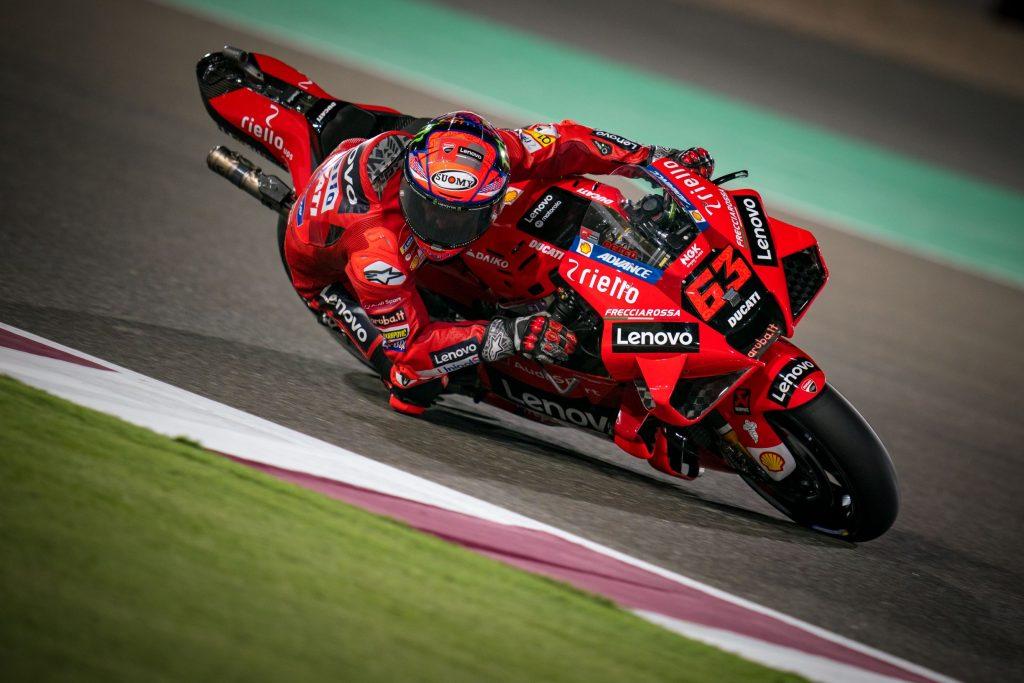 Red-clad Ducati Lenovo MotoGP rider Francesco Bagnaia takes a corner at the 2021 Qatar GP