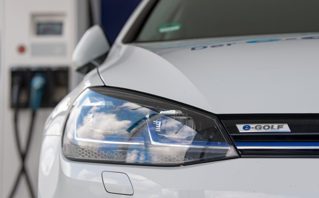 A Volkswagen electric vehicle charges at a charging station
