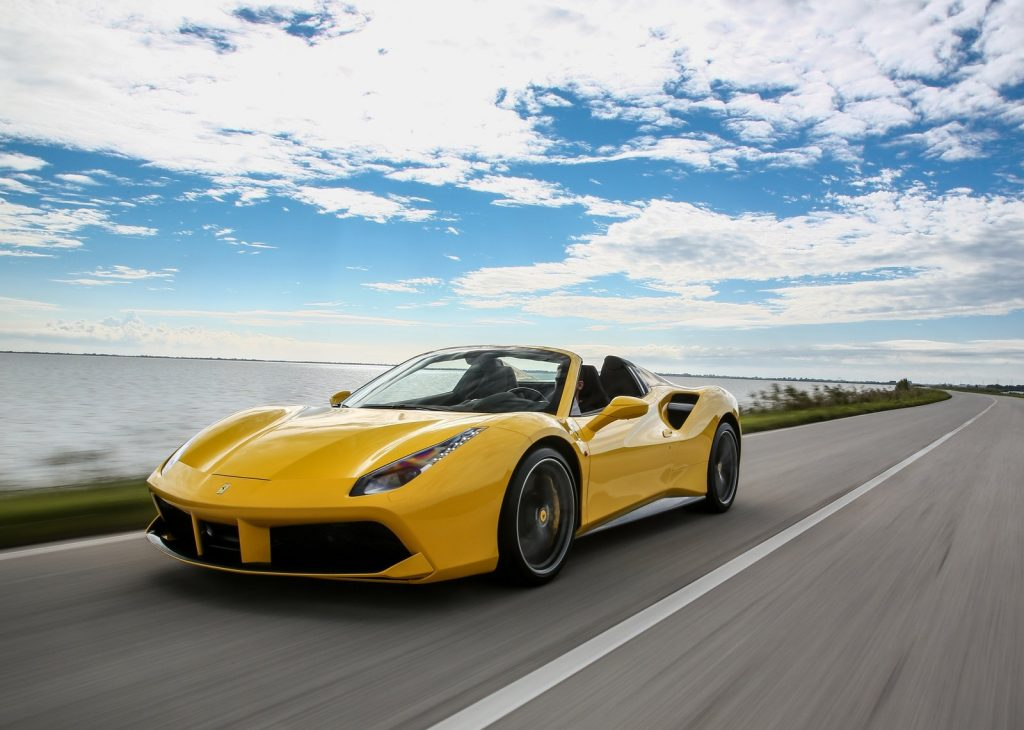 An image of a yellow Ferrari 488 Spider driving down the road.