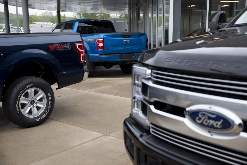 Ford F-150 trucks sit as display cars at a dealership
