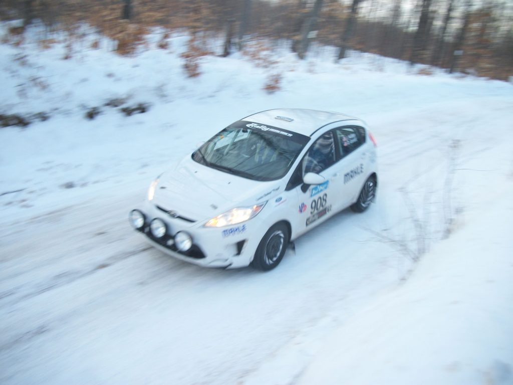 A white Ford Fiesta racing through the snowy forest stage at the 2016 SnoDrift Rally