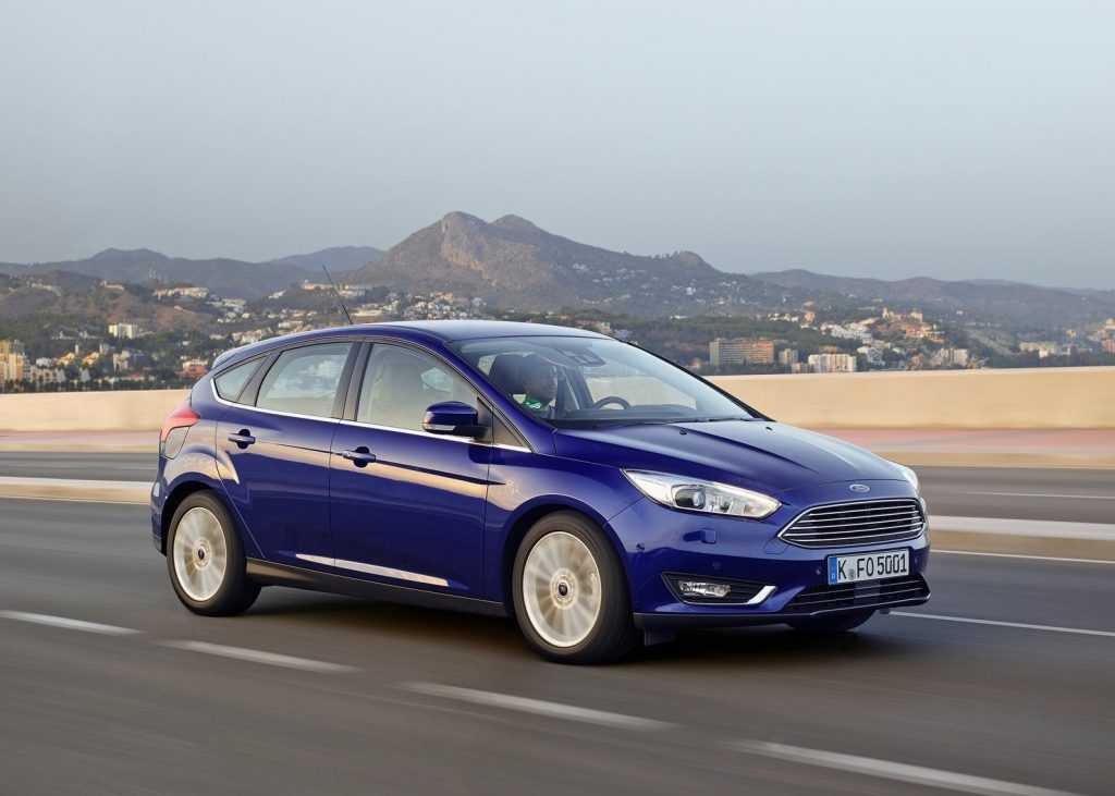 A blue 2015 Ford Focus driving down the road