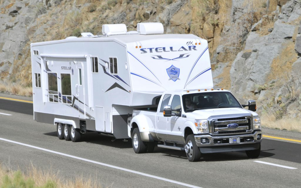 A white Ford F-350 super duty pickup truck towing a camper