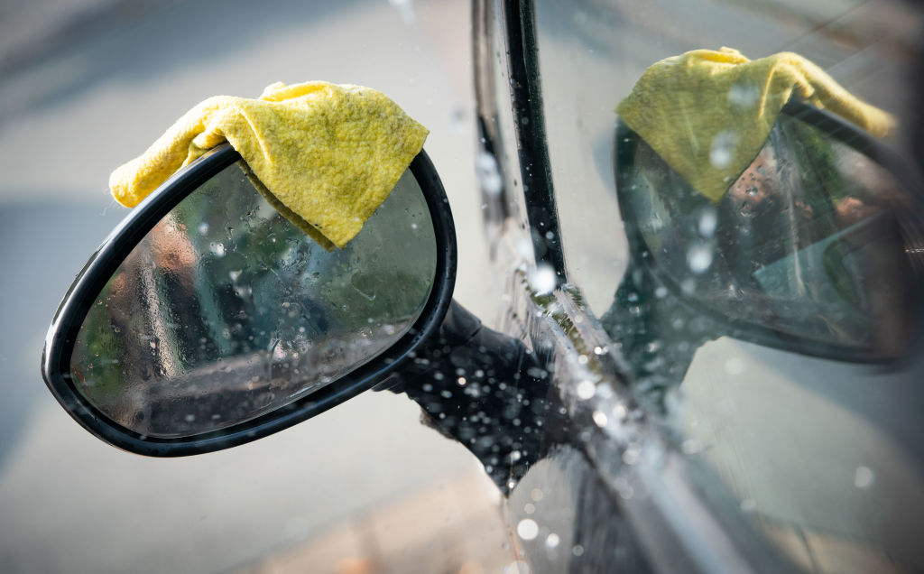 A yellow microfiber towel rests on the sideview mirror of a wet car