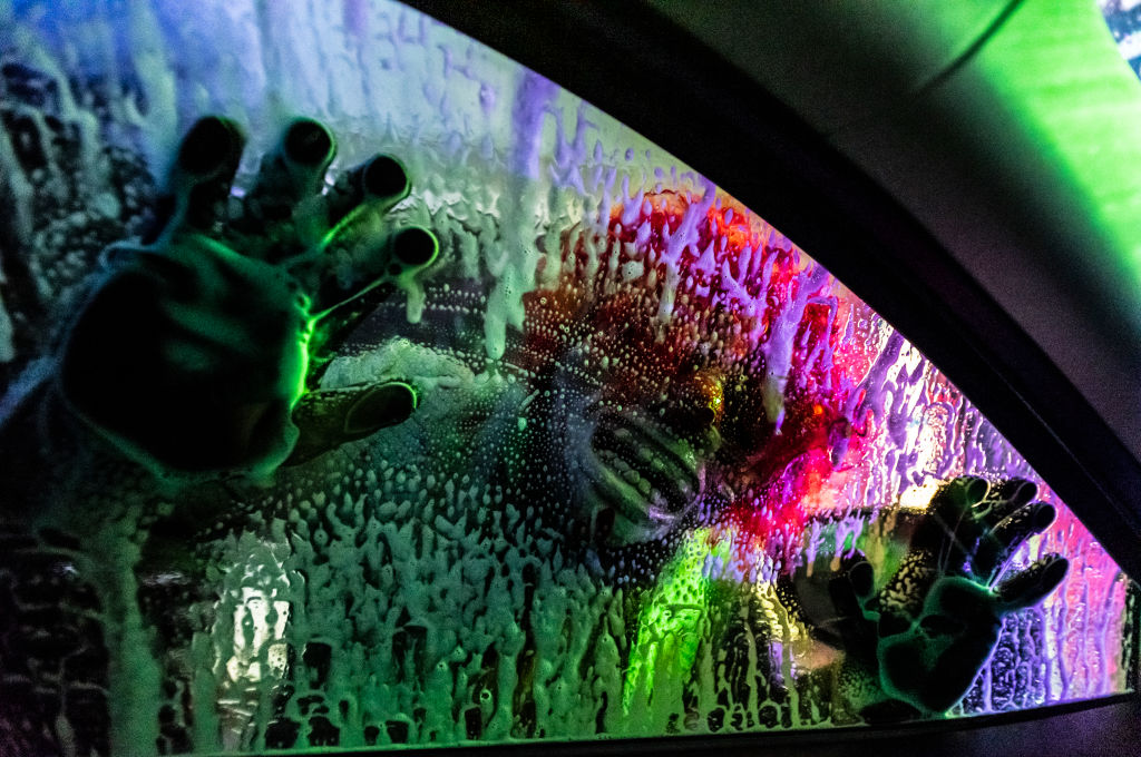 A scare actor presses his face up against a car window in a haunted car wash