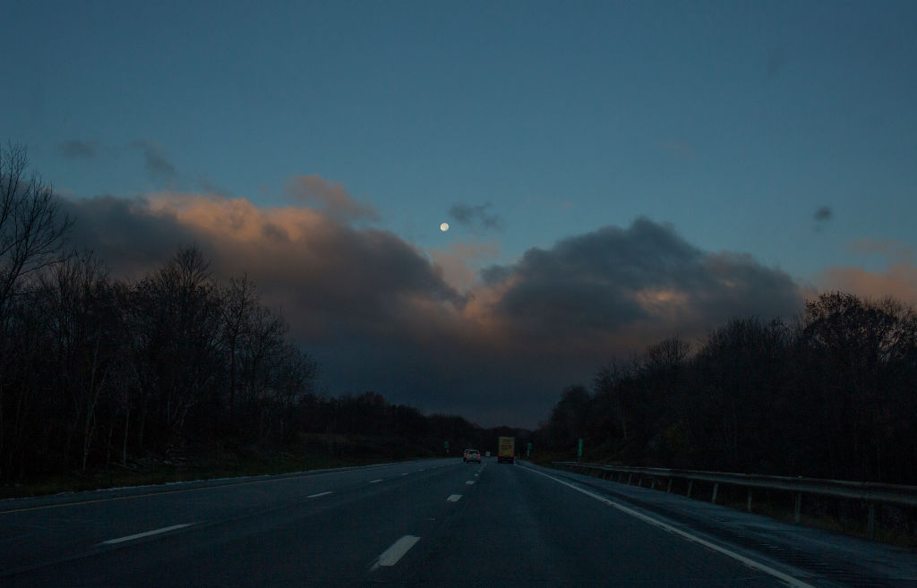 The sun rising over the Pocono Mountains as seen from a car window