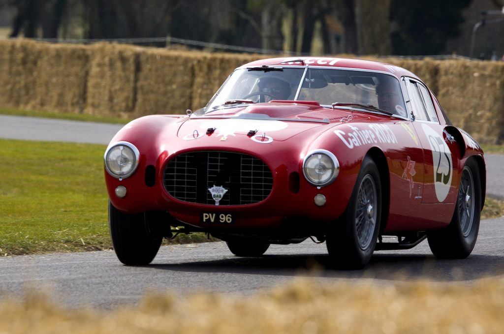 An image of a red Ferrari 375 MM parked outdoors.