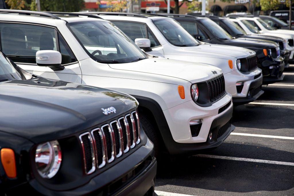 Jeep Renegade SUVs displayed on a dealership sales lot