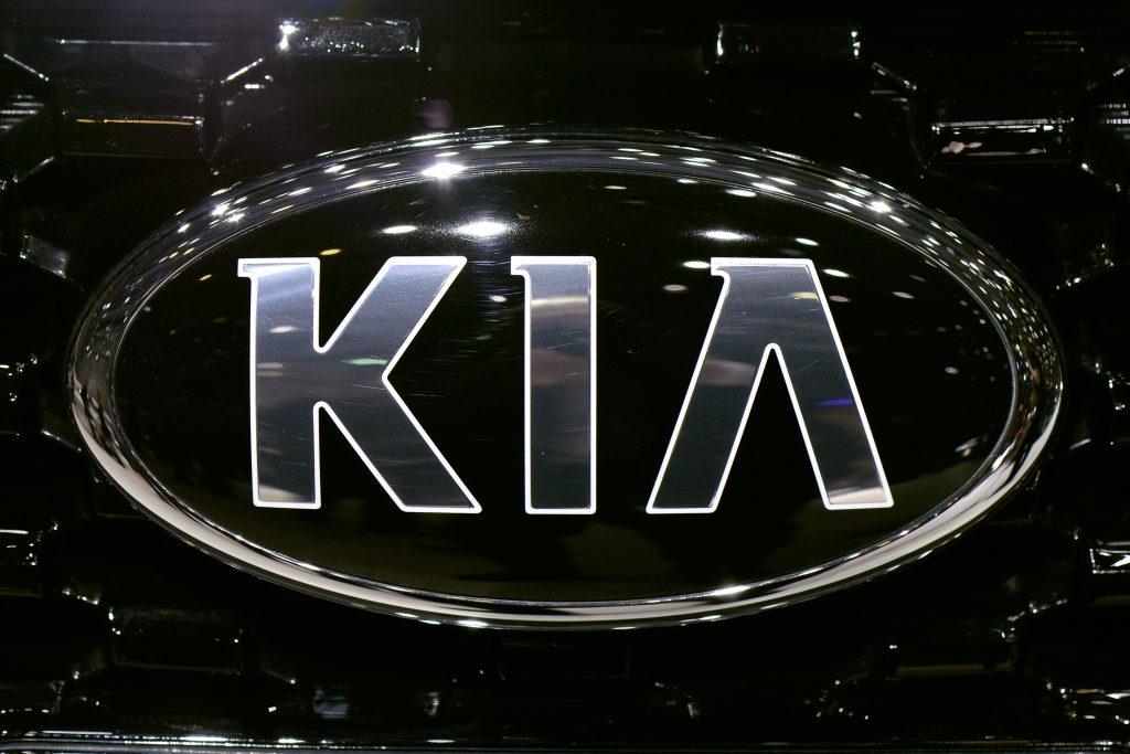 Chrome Kia Motors logo on a black vehicle