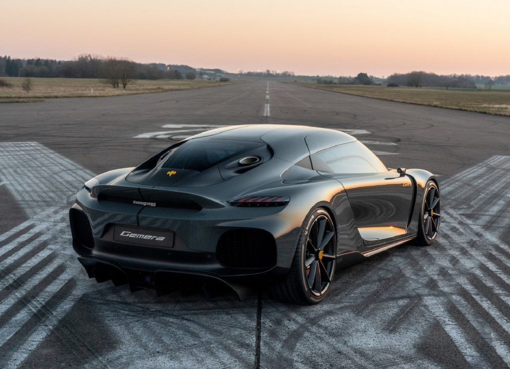 The rear 3/4 view of a gray Koenigsegg Gemera on an airport runway