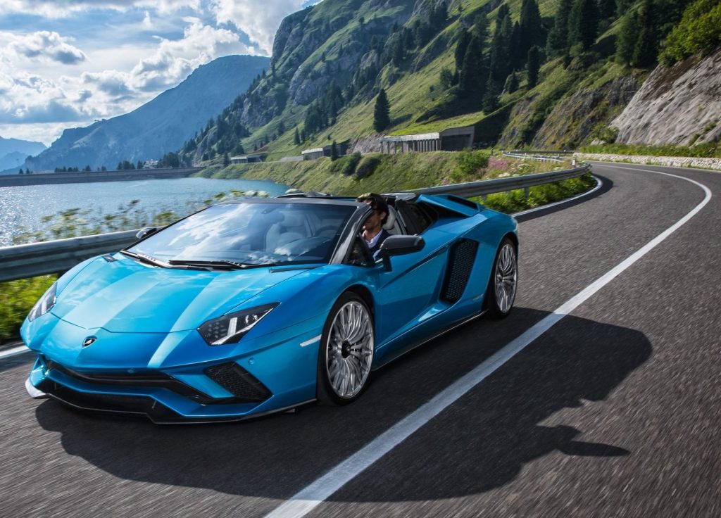 A blue 2018 Lamborghini Aventador driving through the swiss alps with the top down.