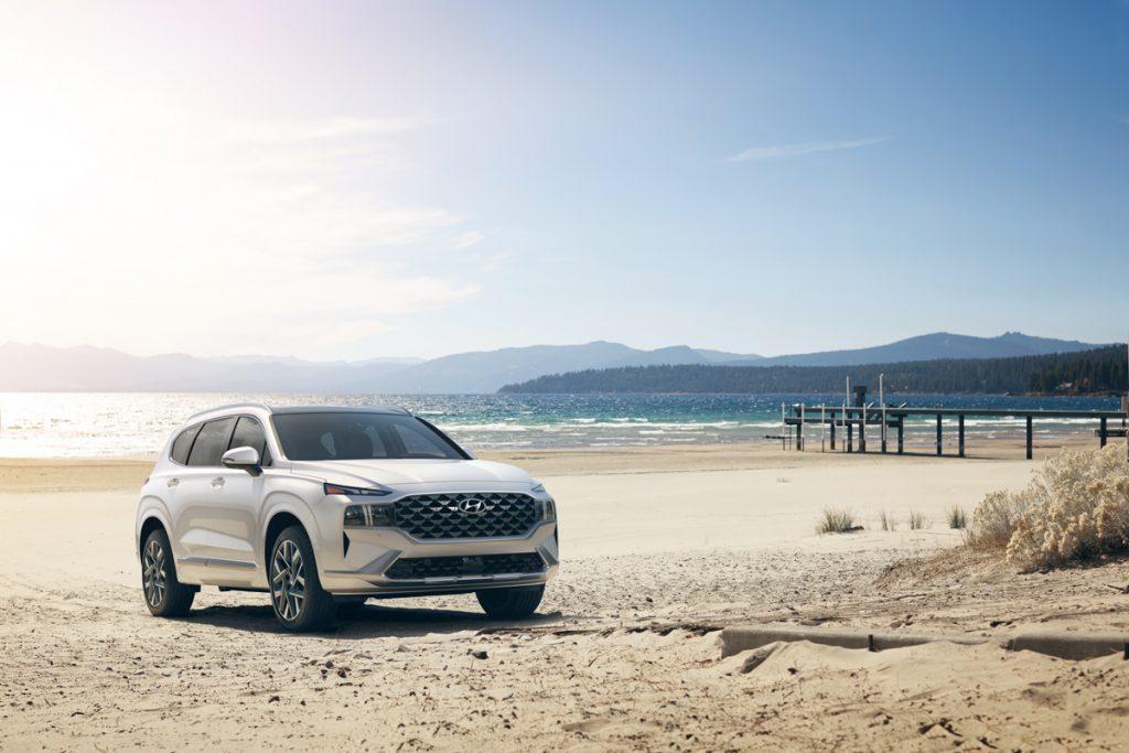 A silver 2021 Hyundai Santa Fe parked in the sand of a beach
