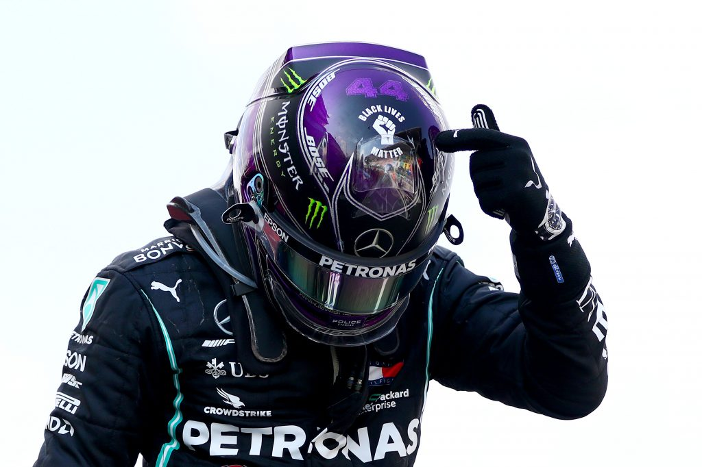 Race winner Lewis Hamilton of Great Britain and Mercedes GP points to the 'Black Lives Matter' symbol on his helmet.