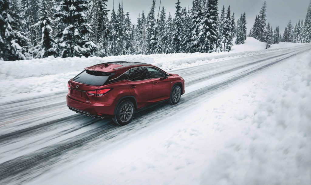 2021 Lexus RX 350, a consumer reports recommended SUV in red driving through the snow