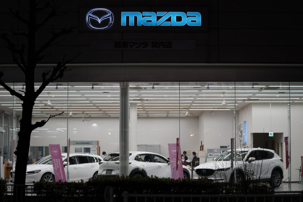 Cars on display in the window of a Mazda dealership