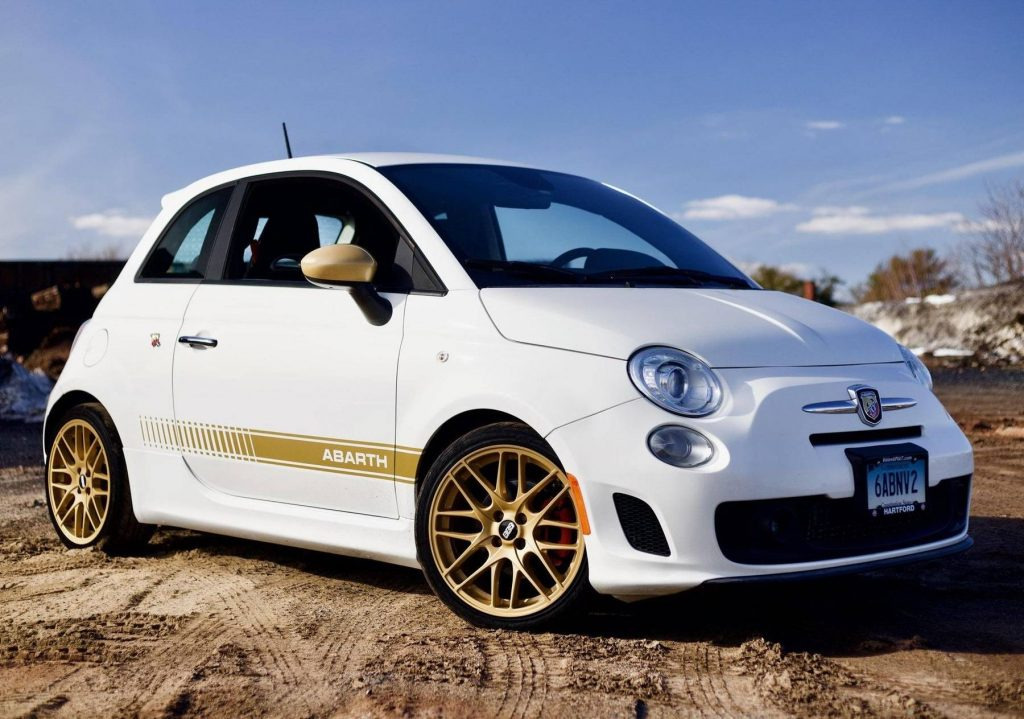 A modified white-and-gold 2013 Fiat 500 Abarth in a snowy dirt field