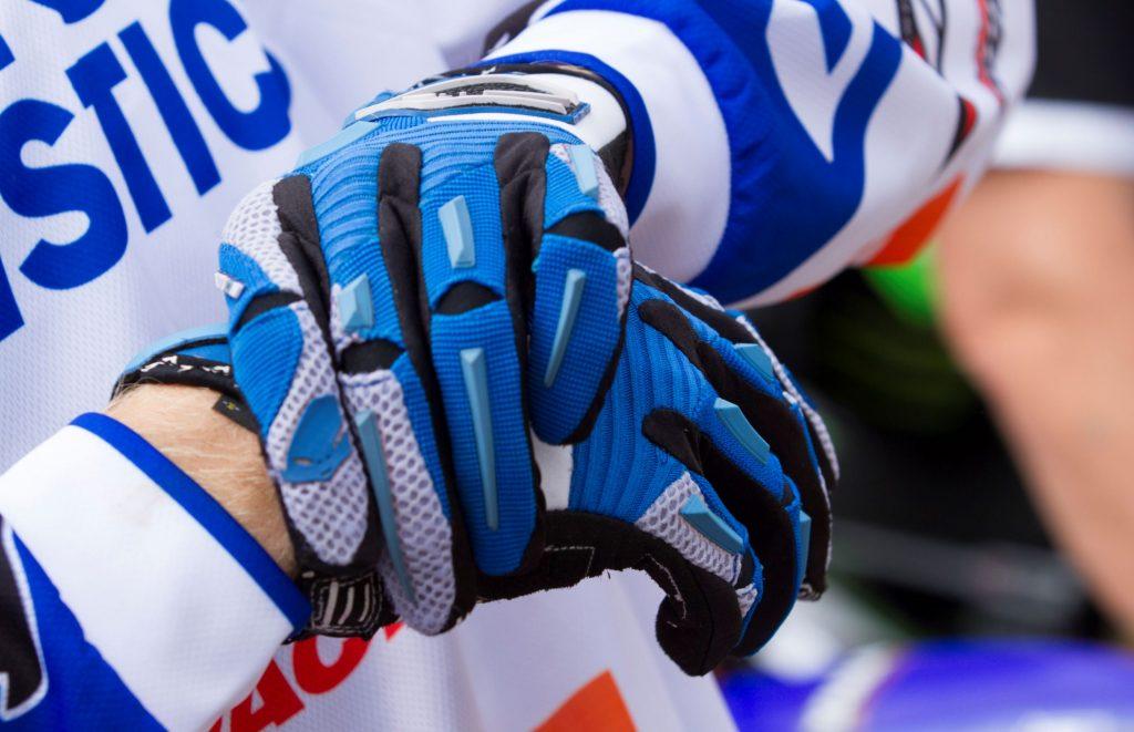 Motocross rider Calvin Vlaanderen puts on his blue riding gloves