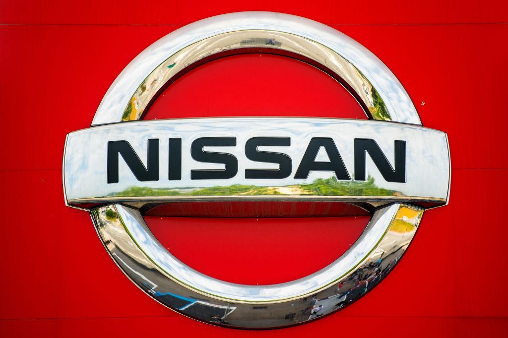 A chrome Nissan logo on a red vehicle