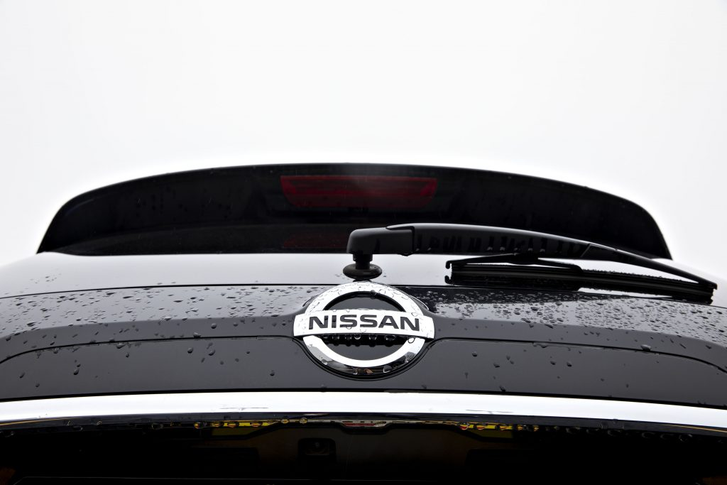 A Nissan logo seen on the back of a Rogue SUV