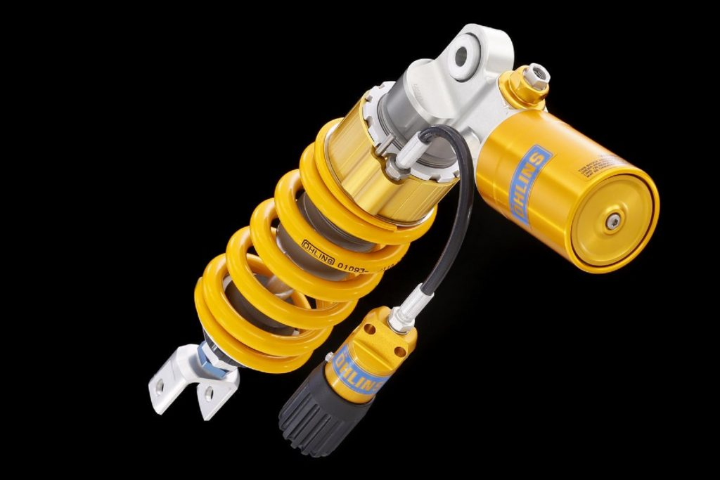 A golden-yellow Ohlins rear motorcycle shock for a 2012 Triumph Street Triple R